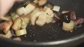 Verdure di torrefazione del cuoco unico con i funghi in una padella Il cuoco unico prepara i piatti vegetariani archivi video