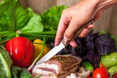 Verdure e fette del bacon con una mano del coltello fotografia stock libera da diritti
