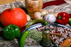 Verdure e legumi sulla tavola Ciotola per frantumare le spezie Zucca gialla, papper verde, cipolla sulla mappa autentica Fotografie Stock