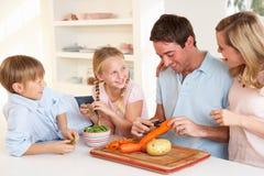 Verdure felici della sbucciatura della famiglia in cucina immagine stock