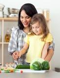 Verdure felici di taglio della figlia e della madre Fotografie Stock