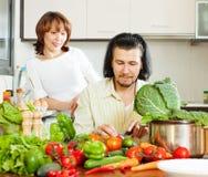 Verdure felici di taglio delle coppie in cucina Fotografia Stock Libera da Diritti