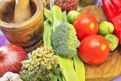 Verdure fresche e sane, rosse e verdi, broccoli, pomodori, cipolla sul tagliere di legno verde oliva e mortale Immagini Stock Libere da Diritti