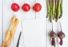 Verdure luminose e una pagina del libro di cucina su fondo bianco Alimento sano per insalata Disposizione piana, vista superiore, fotografia stock