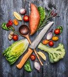Verdure organiche crude con il coltello da cucina ed il cucchiaio di legno di selezione Ingredienti per la cottura sana sul fondo Fotografie Stock