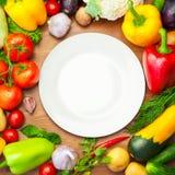 Verdure organiche fresche intorno al piatto bianco Fotografia Stock