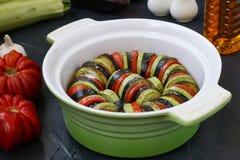 Verdure per la cottura della ratatouille Verdure del taglio: lo zucchini, la melanzana ed i pomodori sono nella forma ceramica fotografie stock