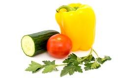 Verdure, pomodori, cetrioli, peperoni e prezzemolo su un bianco Immagine Stock