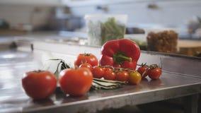 Verdure, pomodori, paprica, porri che si trovano sulla tavola nella cucina commerciale immagine stock libera da diritti