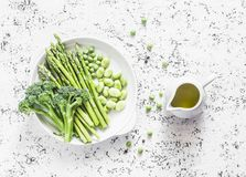 Verdure verdi - asparago, cavolo dei broccoli, piselli, fagiolini e olio d'oliva su fondo leggero, vista superiore Fotografia Stock Libera da Diritti