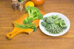 Verdure verdi congelate e fresche differenti su una tavola di cottura Fotografie Stock
