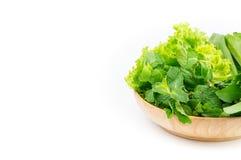 Verdure verdi in piatto di legno su fondo bianco Immagine Stock Libera da Diritti