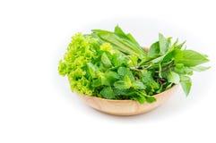 Verdure verdi in piatto di legno su fondo bianco Fotografia Stock