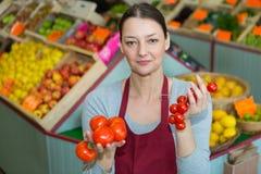 Verdureiro fêmea que guarda dois tomates diferentes das variedades imagem de stock royalty free