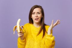 Verdutzte verwirrte junge Frau in den ausgebreiteten Händen der Pelzstrickjacke, frische reife Bananenfrucht halten lokalisiert a stockbild