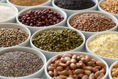 Vereinbarte weiße Schüsseln mit ungekochten Impulsen, Körnern und Samen auf w lizenzfreies stockfoto