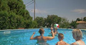 Vereinigte Familie, die aufblasbaren Ball im Hauptpool spielt stock video