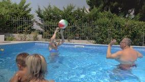 Vereinigte Familie, die Ball im Pool spielt stock footage