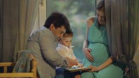 Vereinigte Familie, die das Tablet aufpasst stock video