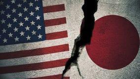 Vereinigte Staaten gegen Japan-Flaggen auf gebrochener Wand Stockbild