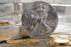 Vereinigte Staaten versilbern Eagle mit Goldmünzen u. Silberbarren im Hintergrund Stockfoto