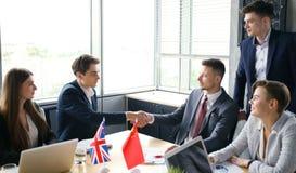 Vereinigtes Königreich und chinesische Führer, die Hände auf einer Abkommenvereinbarung rütteln stockfotografie