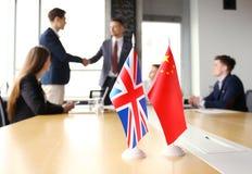 Vereinigtes Königreich und chinesische Führer, die Hände auf einer Abkommenvereinbarung rütteln lizenzfreies stockfoto