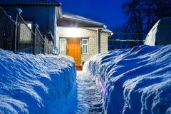 Verengen Sie gegrabene Bahn in der enormen Schneewehe zu einem Haus Lizenzfreies Stockbild