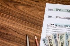 Verenig Staten 1040 belastingsvorm met geld Stock Afbeeldingen