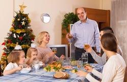 Verenigde familie bij feestelijke lijst Stock Foto