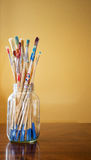 Verf bevlekte penselen in duidelijke kruik stock fotografie
