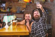 ?verf?r selfie till sociala n?tverk f?r v?nner Man i st?ng som dricker ?l Tagandeselfiefoto som minns stor afton i bar royaltyfria foton