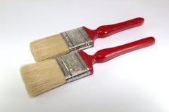 Verf twee borstelt 2 duim breed met rode handvatten op een houten achtergrond Royalty-vrije Stock Foto