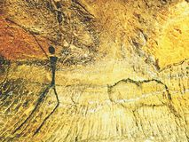 Verf van de menselijke jacht op zandsteenmuur, voorhistorisch beeld Zwarte abstracte kunst in zandsteenhol Stock Afbeeldingen