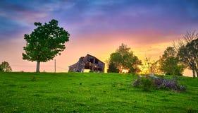 Verfallen Scheune mit Sonnenuntergang stockfotografie