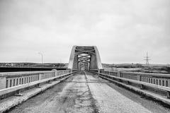 Verfallende Landstraße, die zu verlassene Brücke führt Lizenzfreie Stockfotografie