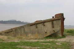 Verfallender konkreter Lastkahn als Rumpf auf Flussbank Stockbilder
