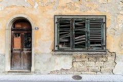 Verfallene alte Hausfassade mit Fensterläden der zerbrochenen Fensterscheibe Lizenzfreie Stockfotos