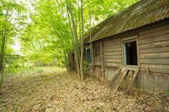 Verfallenes verlassenes Land-Blockhaus, überwältigt durch Bäume, Sperrgebiet nach Tschornobyl-Tragödie Lizenzfreie Stockfotografie