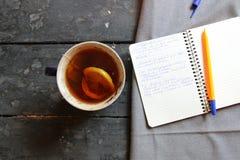 Verfasser oder Schulidee, Tee und Notizbuch auf dem Tisch Lizenzfreie Stockfotos
