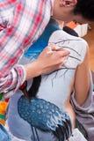 Verfassungskünstler, der auf Rückseite des Mädchens body-painting ist Lizenzfreie Stockbilder