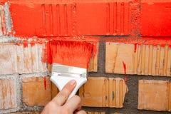 Verfborstel met rode kleur op bakstenen muur Royalty-vrije Stock Afbeelding