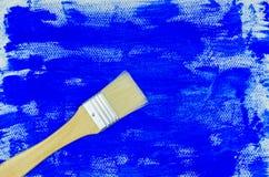 Verfborstel op blauwe het schilderen achtergrond Stock Afbeeldingen