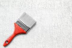 Verfborstel op de witte ruwe oppervlakte Het hulpmiddel van de bouw Royalty-vrije Stock Afbeeldingen