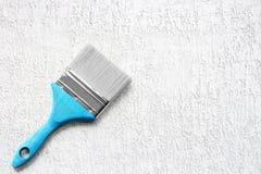 Verfborstel op de witte ruwe oppervlakte Het hulpmiddel van de bouw Stock Afbeelding