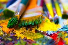 Verfborstels aan het het schilderen palet met kleuren Royalty-vrije Stock Afbeelding