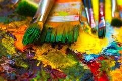 Verfborstels aan het het schilderen palet met kleuren Stock Foto's