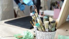 Verfborstels in een emmer De kunstenaar bereidt een beeld voor stock videobeelden