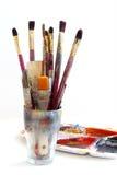 Verfborstels in een glas en een palet met kleuren, op wh worden geïsoleerd die Royalty-vrije Stock Foto's