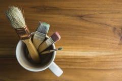 Verfborstels in een koffiekop stock foto